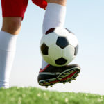 Horizontal image of soccer ball being kicked by footballer